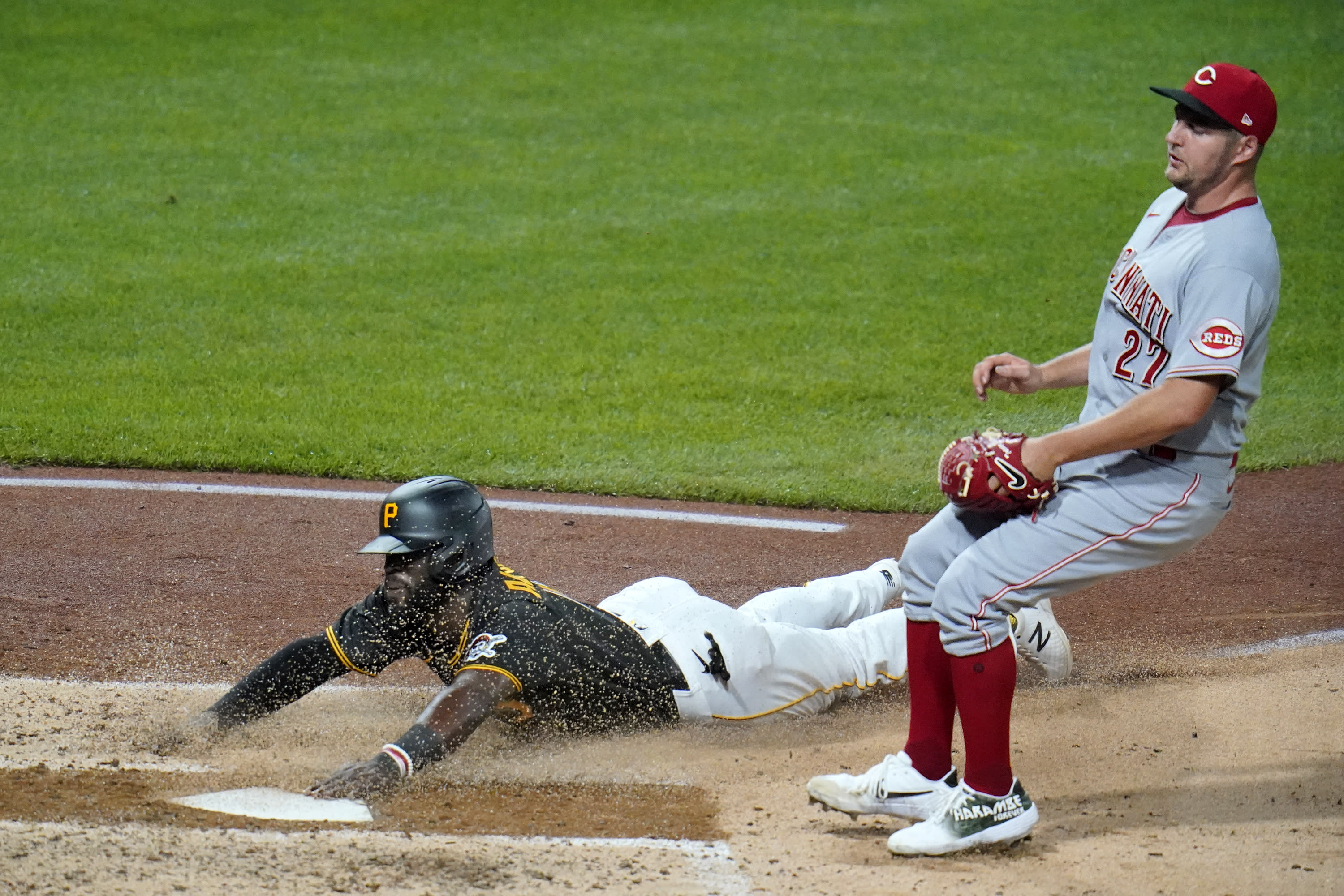 Pittsburgh Pirates' Anthony Alford, left, scores on a wild pitch as Cincinnati Reds starting pitcher Trevor Bauer covers home on the play during the fourth inning of the second baseball game of a doubleheader in Pittsburgh, Friday, Sept. 4, 2020. (AP Photo/Gene J. Puskar)