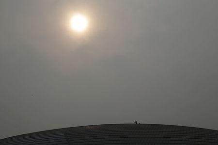 A worker cleans the roof of National Grand Theatre on a polluted day in Beijing, China, February 15, 2017. REUTERS/Jason Lee
