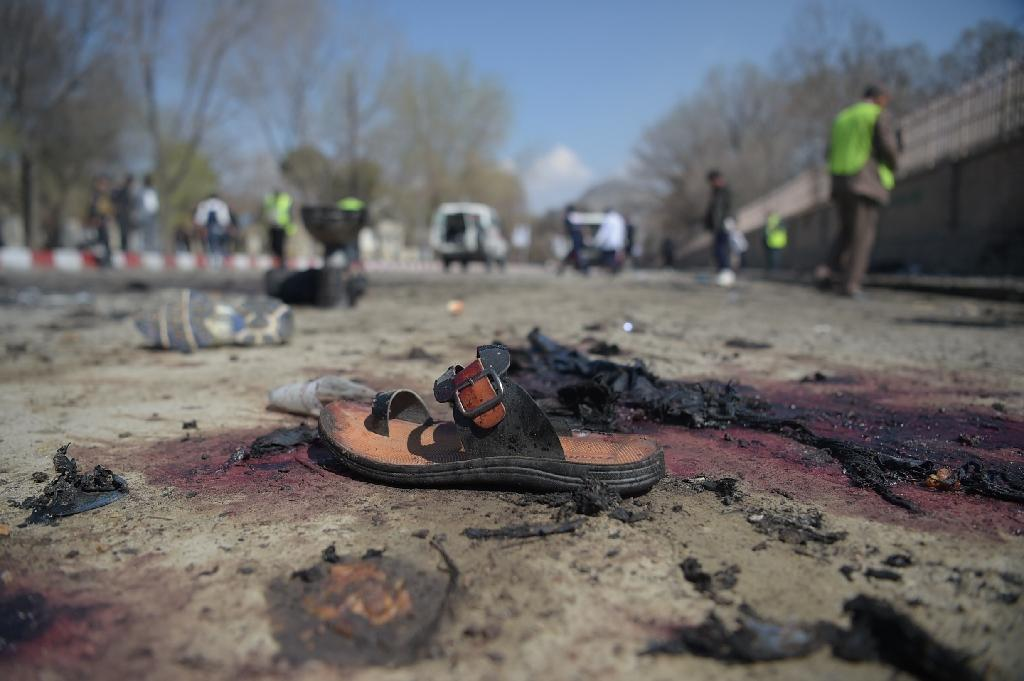 In a photograph taken by AFP's Shah Marai, who was killed covering a suicide bombing on Monday, a sandal is seen laying on the ground along a road at the site of a suicide bombing attack in Kabul on March 21, 2018 (AFP Photo/SHAH MARAI)