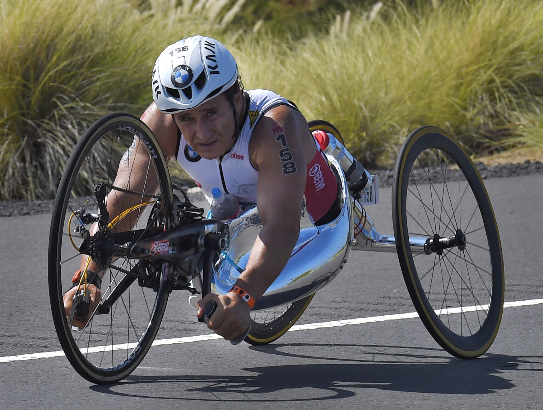 FILE - In this Oct. 10, 2015, file photo, Alex Zanardi, of Italy, rides during the cycling portion of the Ironman World Championship Triathlon, in Kailua-Kona, Hawaii. Zanardi has accomplished more since he lost both of his legs in a gruesome auto racing crash than many racers do in a lifetime. The latest achievement for the two-time CART champion and four-time Paralympic gold medalist is this weekend's Rolex 24 at Daytona endurance race. (AP Photo/Mark J. Terrill, File)