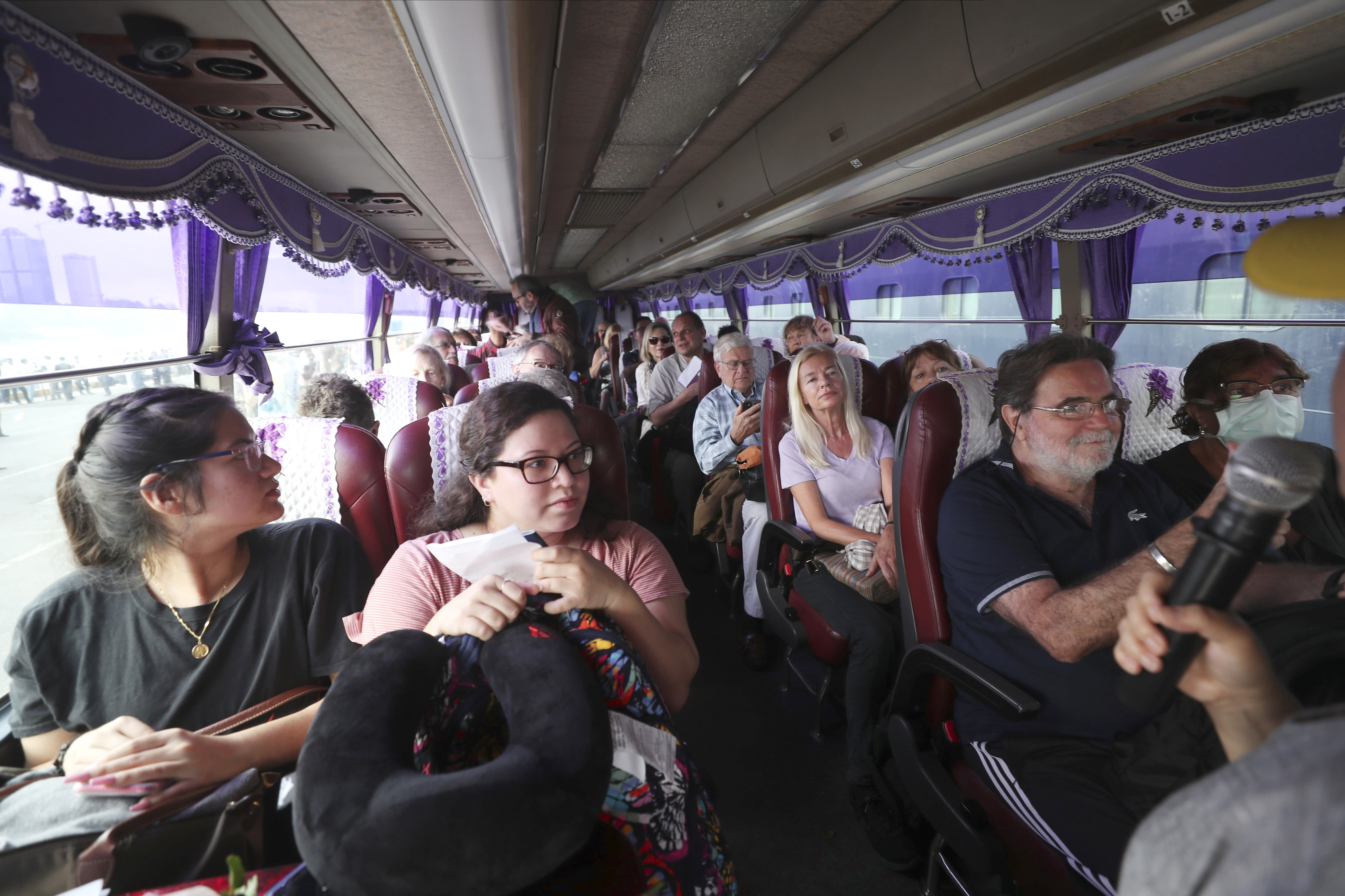 Passengers of the MS Westerdam sit in a busa after they disembarked from the cruise ship, owned by Holland America Line, at the port of Sihanoukville, Cambodia, Friday, Feb. 14, 2020. Hundreds of cruise ship passengers long stranded at sea by virus fears cheered as they finally disembarked Friday and were welcomed to Cambodia. (AP Photo/Heng Sinith)