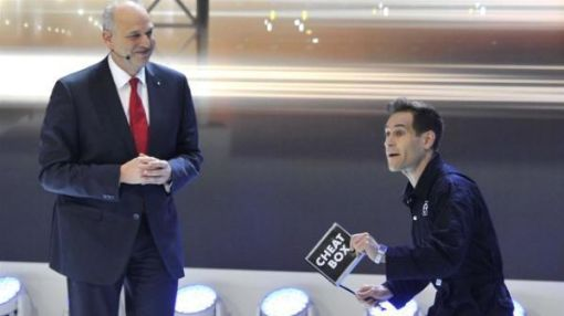 Protestor Jumps IntoVolkswagen Auto Show Presentation With'Cheat Box'