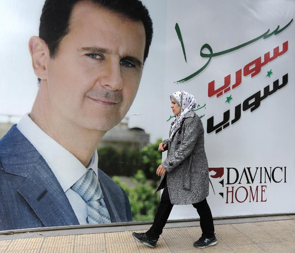 A Syrian woman walks past a placard bearing a portrait of President Bashar al-Assad in the city of Damascus (AFP Photo/Louai Beshara)