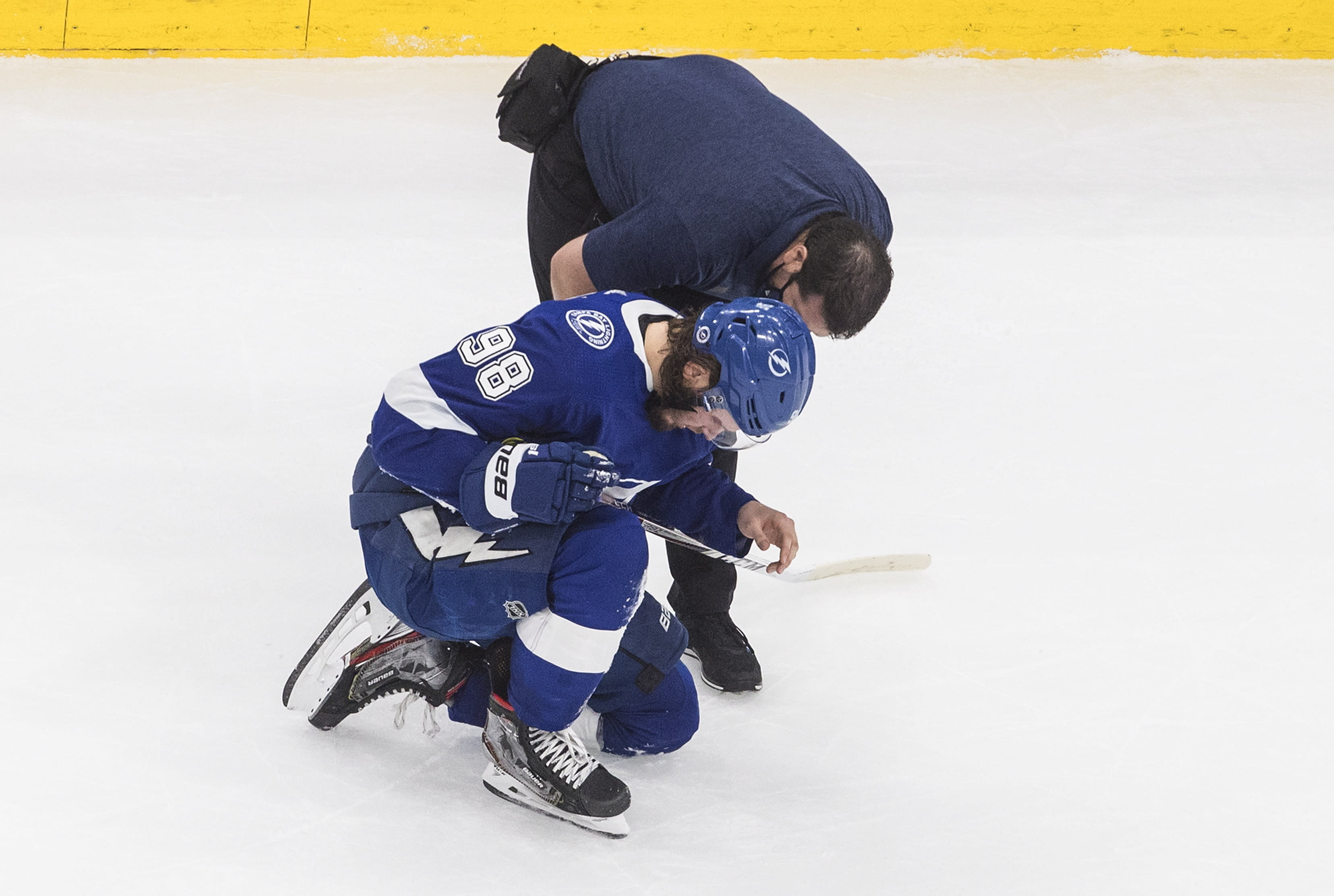 A trainer talks with Tampa Bay Lightning defenseman Mikhail Sergachev (98) after he was injured by a high stick during the third period against the New York Islanders in Game 5 of the NHL hockey Eastern Conference final, Tuesday, Sept. 15, 2020, in Edmonton, Alberta. (Jason Franson/The Canadian Press via AP)