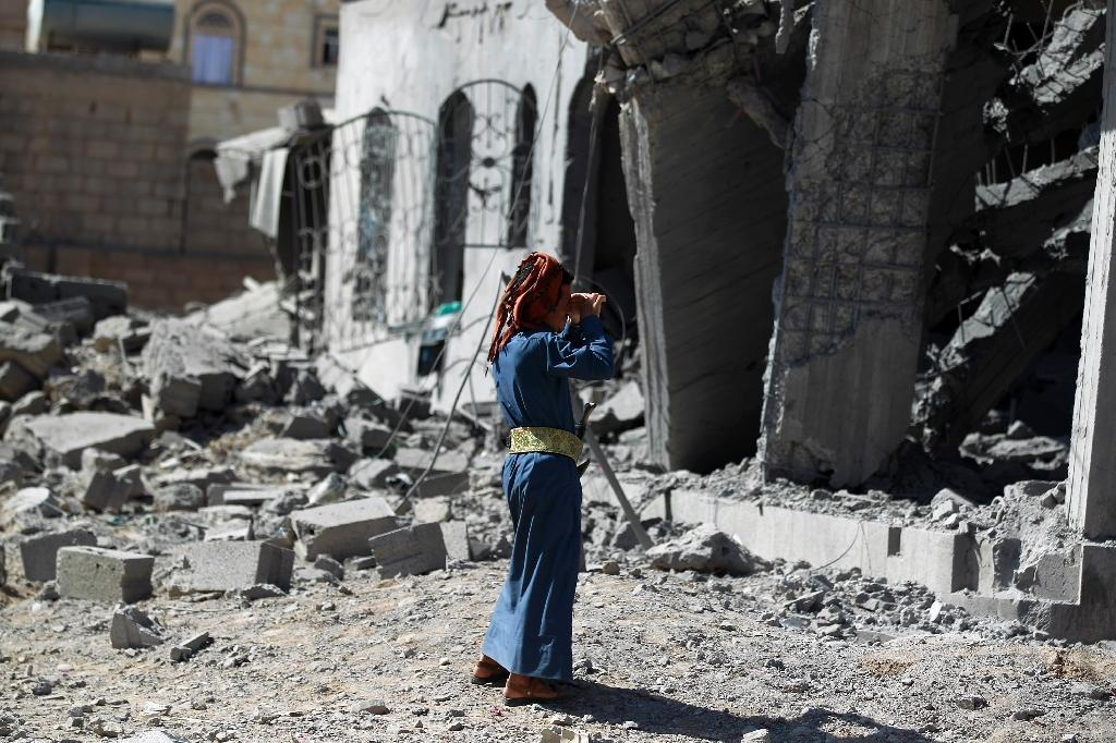 A Yemeni man stands next to the ruins of buildings destroyed in an air strike by the Saudi-led coalition in the capital Sanaa on October 28, 2015 (AFP Photo/Mohammed Huwais)