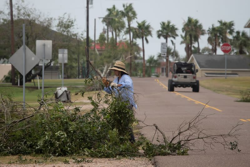 A resident clears debris after returning to her home in the aftermath of Hurricane Hanna in Port Mansfield, Texas