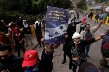 An opposition supporter holds up the Constitution of the Republic of Honduras during a protest over a contested presidential election with allegations of electoral fraud in Tegucigalpa, Honduras, December 22, 2017. REUTERS/Jorge Cabrera