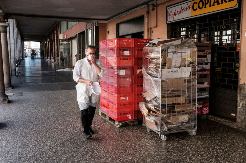 FILE PHOTO: A supermarket worker adjusts a protective face mask as he walks past shops in Casalpusterlengo