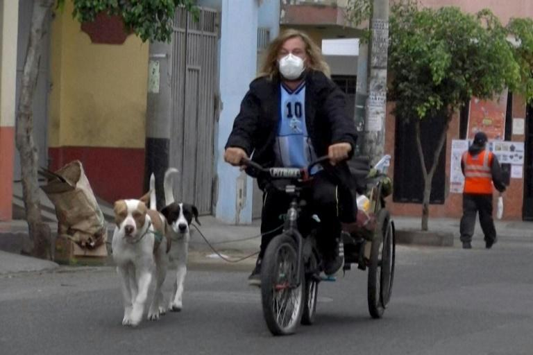 In this AFPTV screen grab Argentine Michael Graef rides his tricycle followed by his dogs in Lima, on June 11, 2020