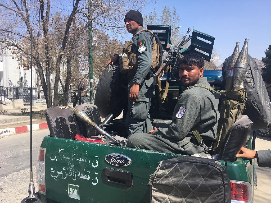 Afghan policemen near the site where a suicide bomber blew himself up in front of Kabul University, killing at least eight people as Afghans celebrate the Persian new year holiday (AFP Photo/Shah MARAI)