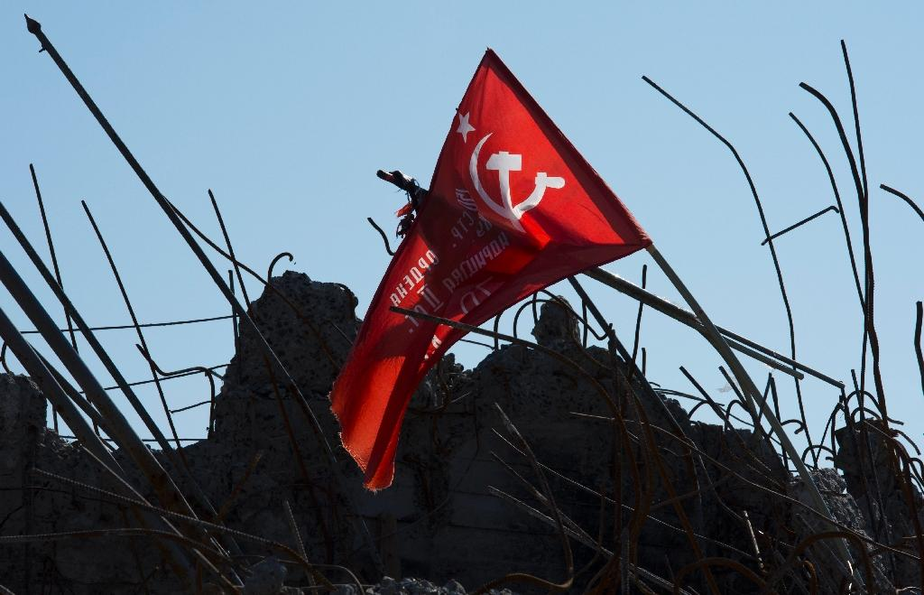 A Soviet-era flag flutters above rubble at the top of the destroyed Savur Mohyla memorial in Snizhne, Ukraine, on September 26, 2014 (AFP Photo/John MacDougall)