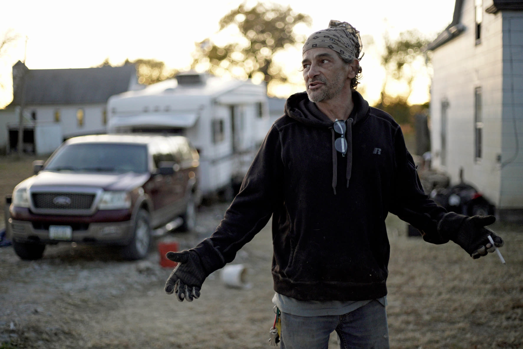 In this Tuesday, Oct. 22, 2019 photo, Marty Study gestures in Bartlett, Iowa, in front of the trailer he has lived in since the March floods. Study said he was rescued from his home, right rear, after floodwaters reached the second floor. Flooding along the Missouri River has stretched on for seven months in places and could endure through the winter, leaving some Upper Midwest farmland and possibly some homes encased in ice. (AP Photo/Nati Harnik)