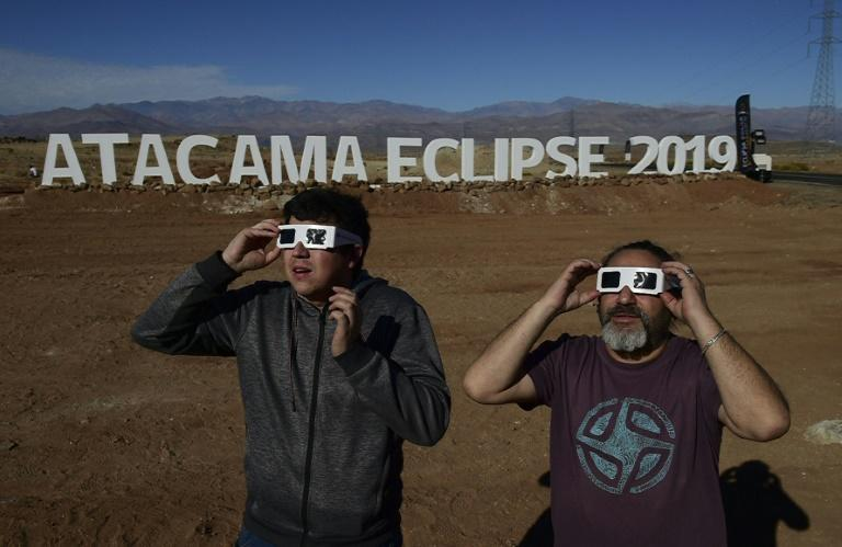 Tourists try special glasses at the entrance of an astronomical camp where thousands will observe the July 2 total solar eclipse in the Atacama desert commune of Vallenar (AFP Photo/MARTIN BERNETTI)