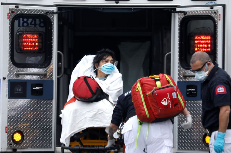 Woman loaded into ambulance in Harlem neighbourhood of Manhattan during outbreak of coronavirus in New York