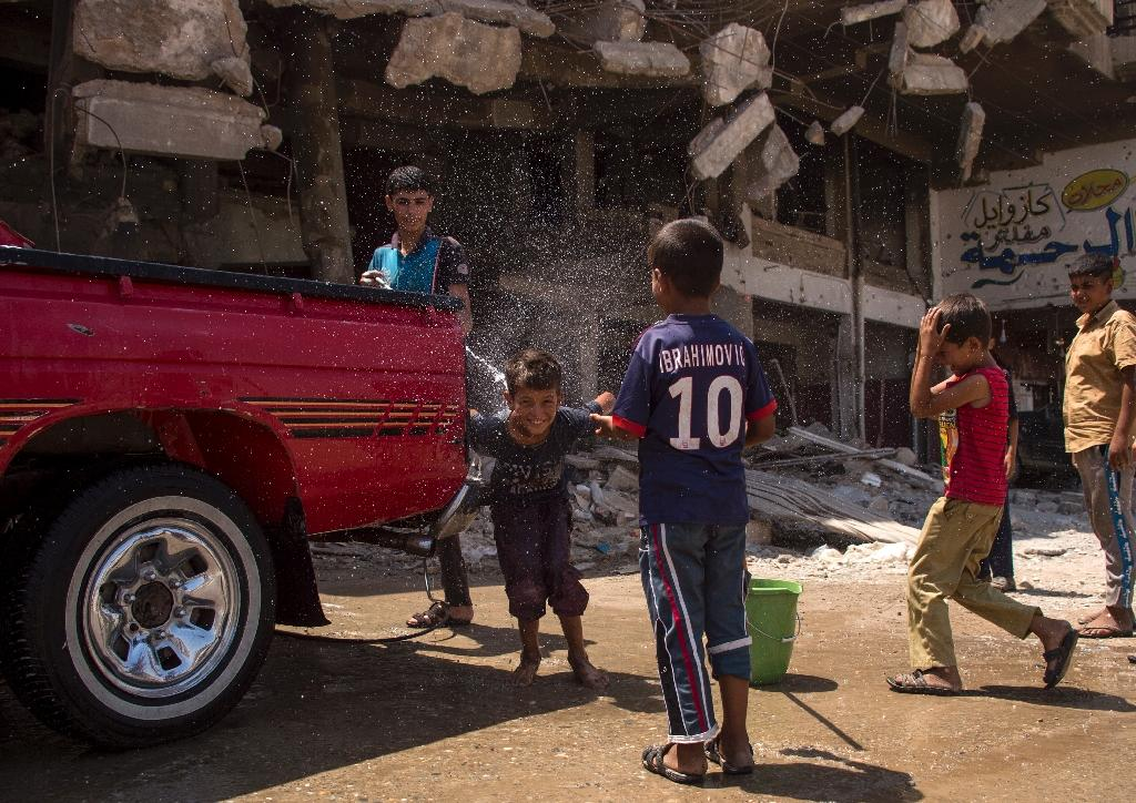 Iraqi boys wash a vehicle in west Mosul on July 12, 2017, days after the government announced the recapture of the city from the Islamic State group (AFP Photo/FADEL SENNA)