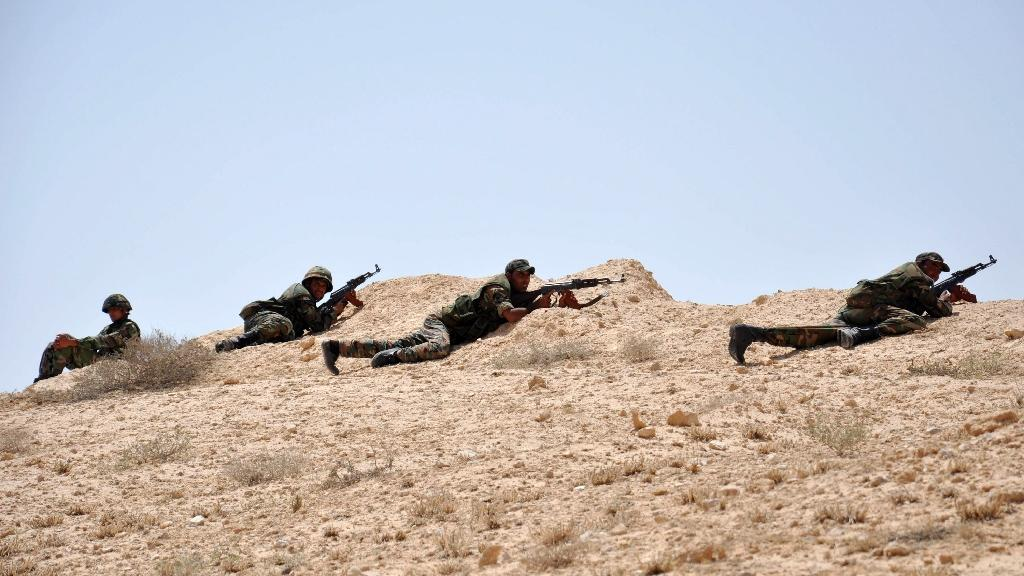 Syrian soldiers get in position during clashes with Islamic State jihadists on the outskirts of Palmyra, on May 17, 2015 (AFP Photo/)