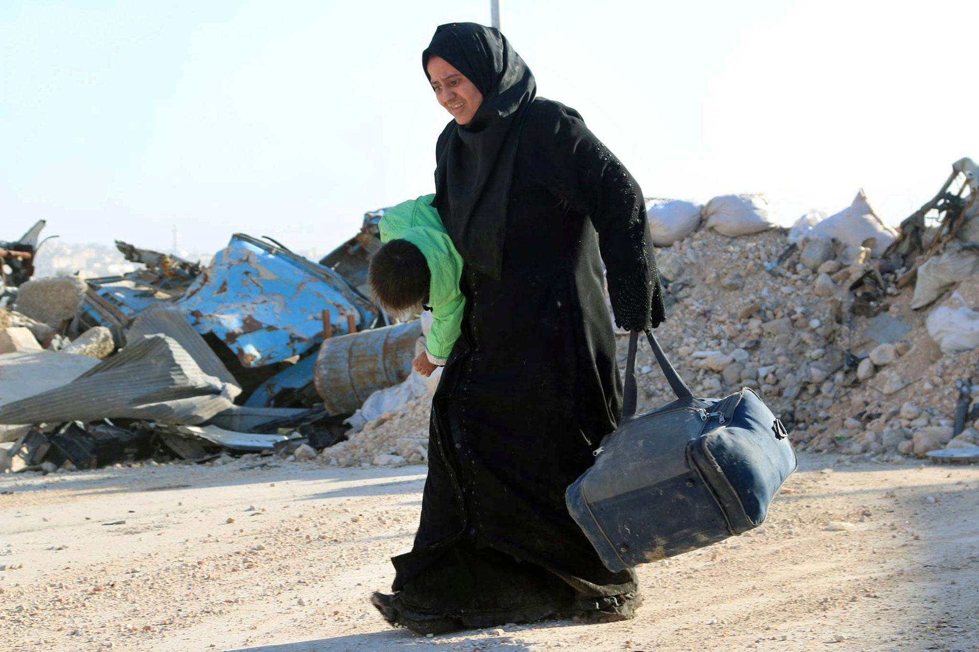 <p>This Sunday, Nov. 27, 2016 photo provided by the Rumaf, a Syrian Kurdish activist group, which has been authenticated based on its contents and other AP reporting, shows A Syrian woman carrying her child in one hand and a bag in the other, as she flees rebel-held eastern neighborhoods of Aleppo into the Sheikh Maqsoud area that is controlled by Kurdish fighters, Syria. Syrian state media is reporting that government forces have captured the eastern Aleppo neighborhood of Sakhour, putting much of the northern part of Aleppo's besieged rebel-held areas under state control. (The Rumaf via AP) </p>