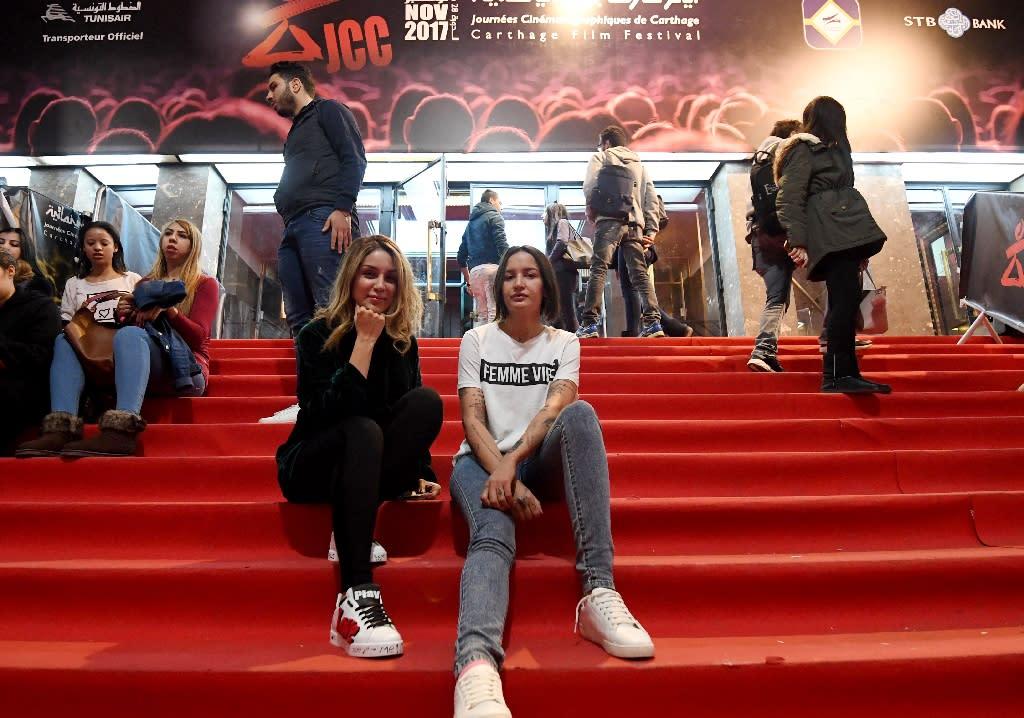 Tunisian activist Amina Sboui (R) poses with Tunisian director Nada Mezni Hafaiedh (L) outside a cinema on November 8, 2017, during the 28th edition of the Carthage Film Festival