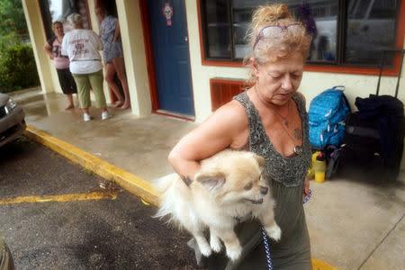 Lenora Adams loads up her dog as she evacuates a motel as Hurricane Michael comes ashore in Panacea, Florida, U.S., October 10, 2018. REUTERS/Carlo Allegri