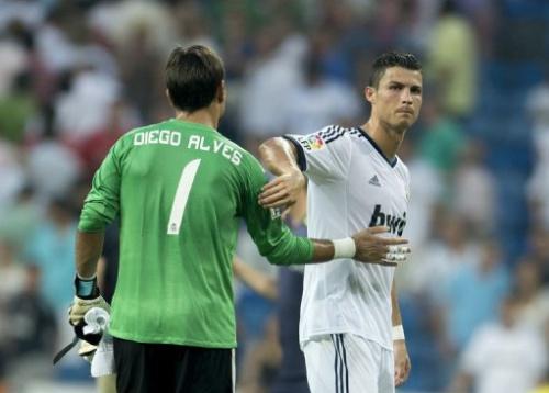 El delantero del Real Madrid Cristiano Ronaldo (D) saluda al guardameta brasileño de su equipo Diego Alves