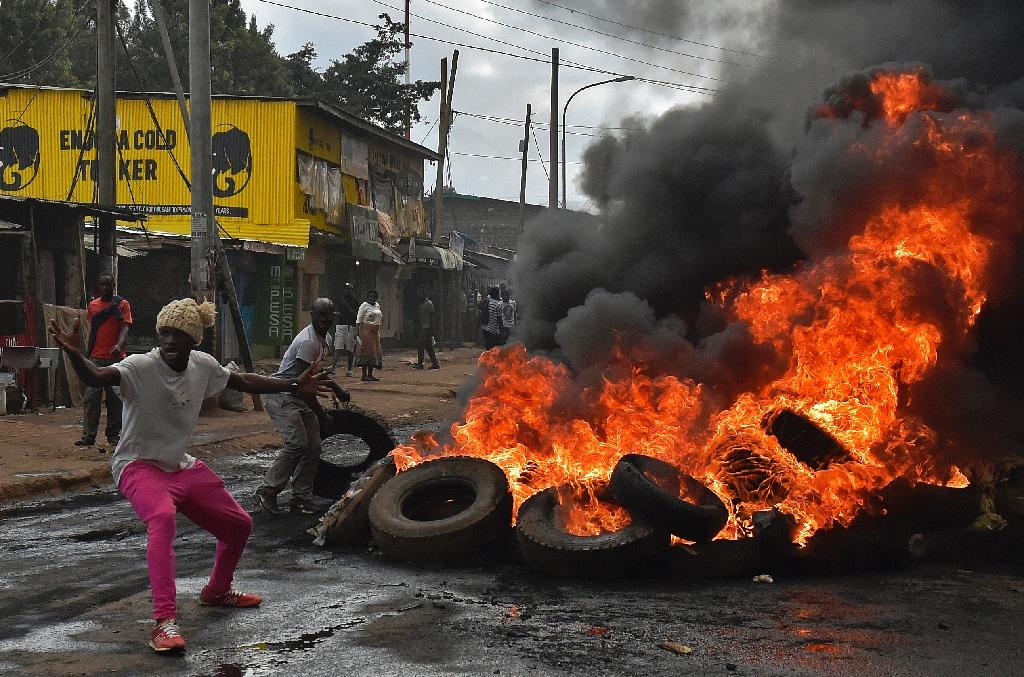 Kenyan opposition activists set fire to barricades during a protest against the election commission in Nairobi, on May 23, 2016