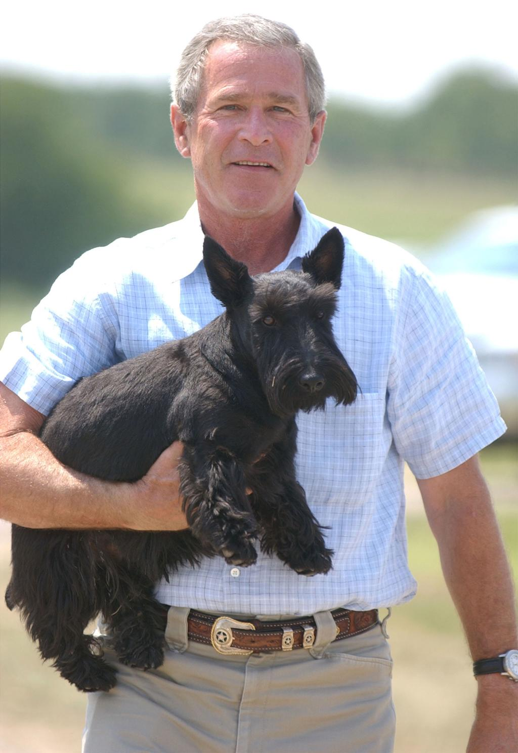 U.S. President George W. Bush carries his dog, Barney, after meeting with the media near his ranch August 13, 2003 in Crawford, Texas. President Bush met with his economic team at his Texas ranch. (Photo by Duane A. Laverty-Pool/Getty Images)