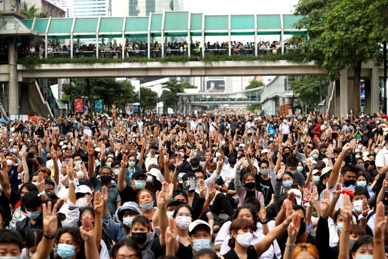 Pro-democracy protesters show the three-finger salute as they gather demanding the government to resign and to release detained leaders in Bangkok
