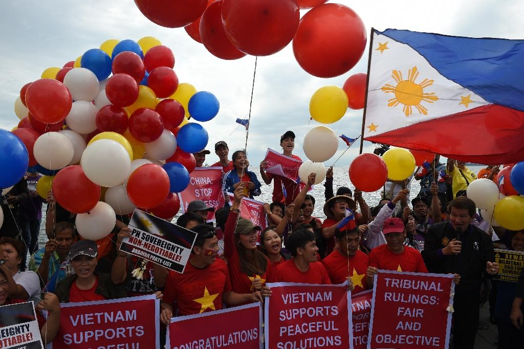Filipino activists and Vietnamese nationals celebrate on Roxas Boulevard in Manila, on July 12, 2016 (AFP Photo/Ted Aljibe)