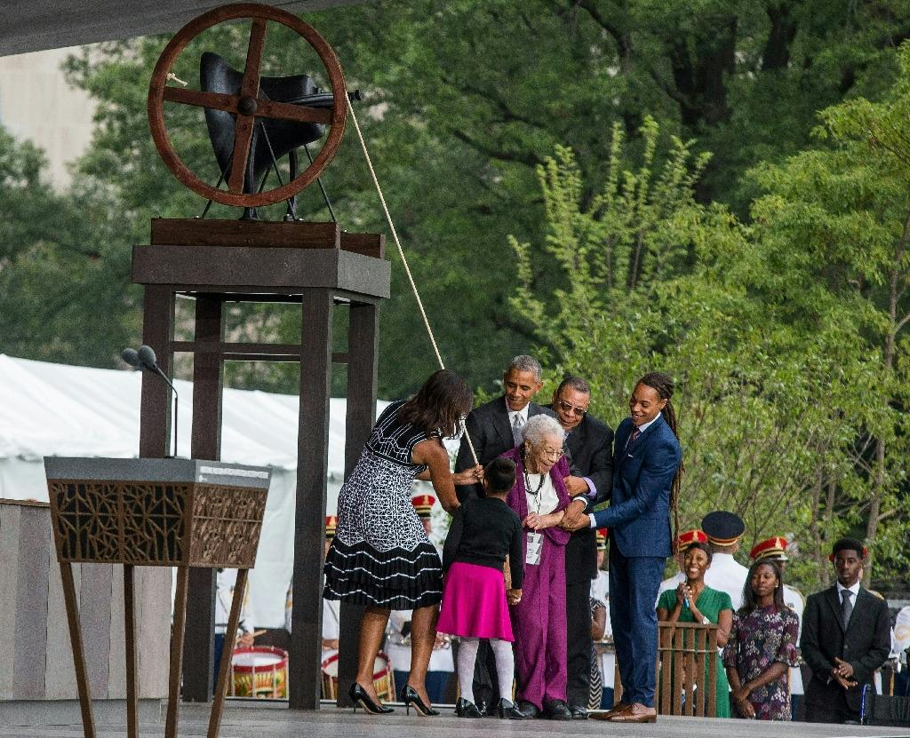 US President Barack Obama and Ruth Odom Bonner (purple) , along with her family and US First Lady Michelle Obama (L), ring a bell to mark the opening of the Smithsonian National Museum of African American History and Culture, on September 24, 2016 (AFP Photo/Zach Gibson)