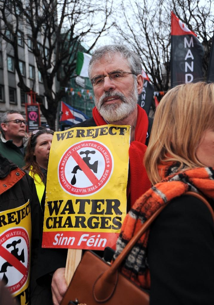 Sinn Fein leader Gerry Adams holds an anti-water charges placard during a march in Dublin, Ireland, on February 20, 2016 protesting against water charges and calling for an end to austerity (AFP Photo/Caroline Quinn)