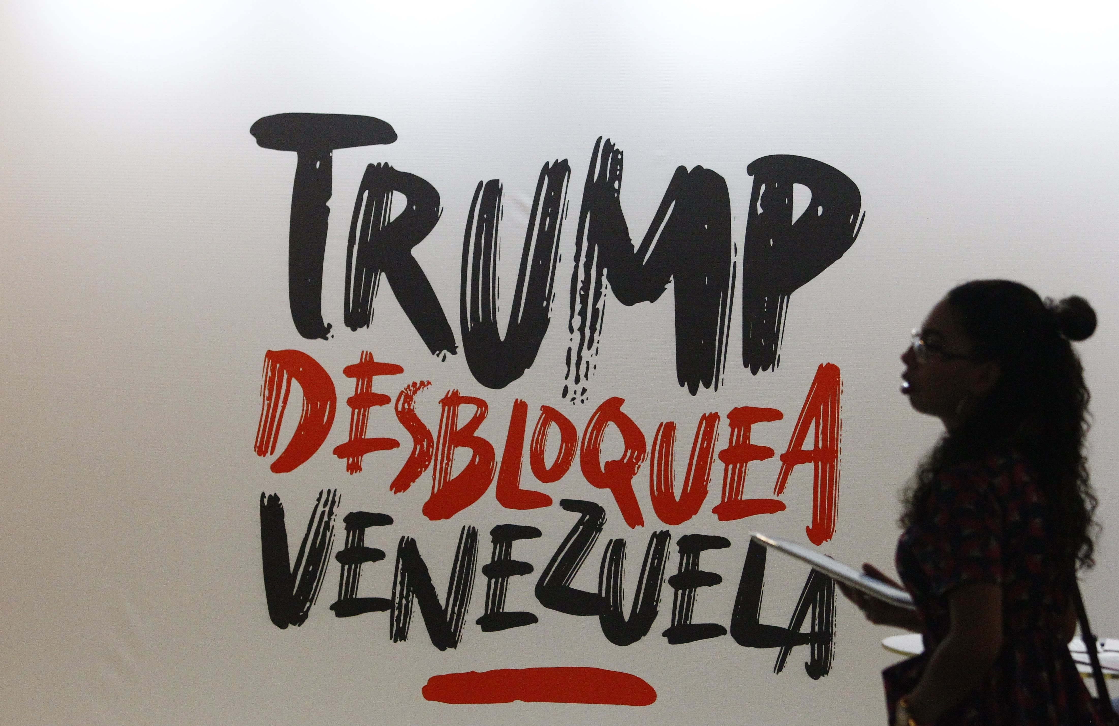 """A woman walks next to a sign that reads in Spanish """"Trump, Unblock Venezuela,"""" a reference to the Venezuelan government view that U.S. sanctions, aimed at toppling President Nicolas Maduro, are driving the country's economic problems, at the Sao Paulo Forum in Caracas, Venezuela, Friday, July 26, 2019. (AP Photo/Leonardo Fernandez)"""
