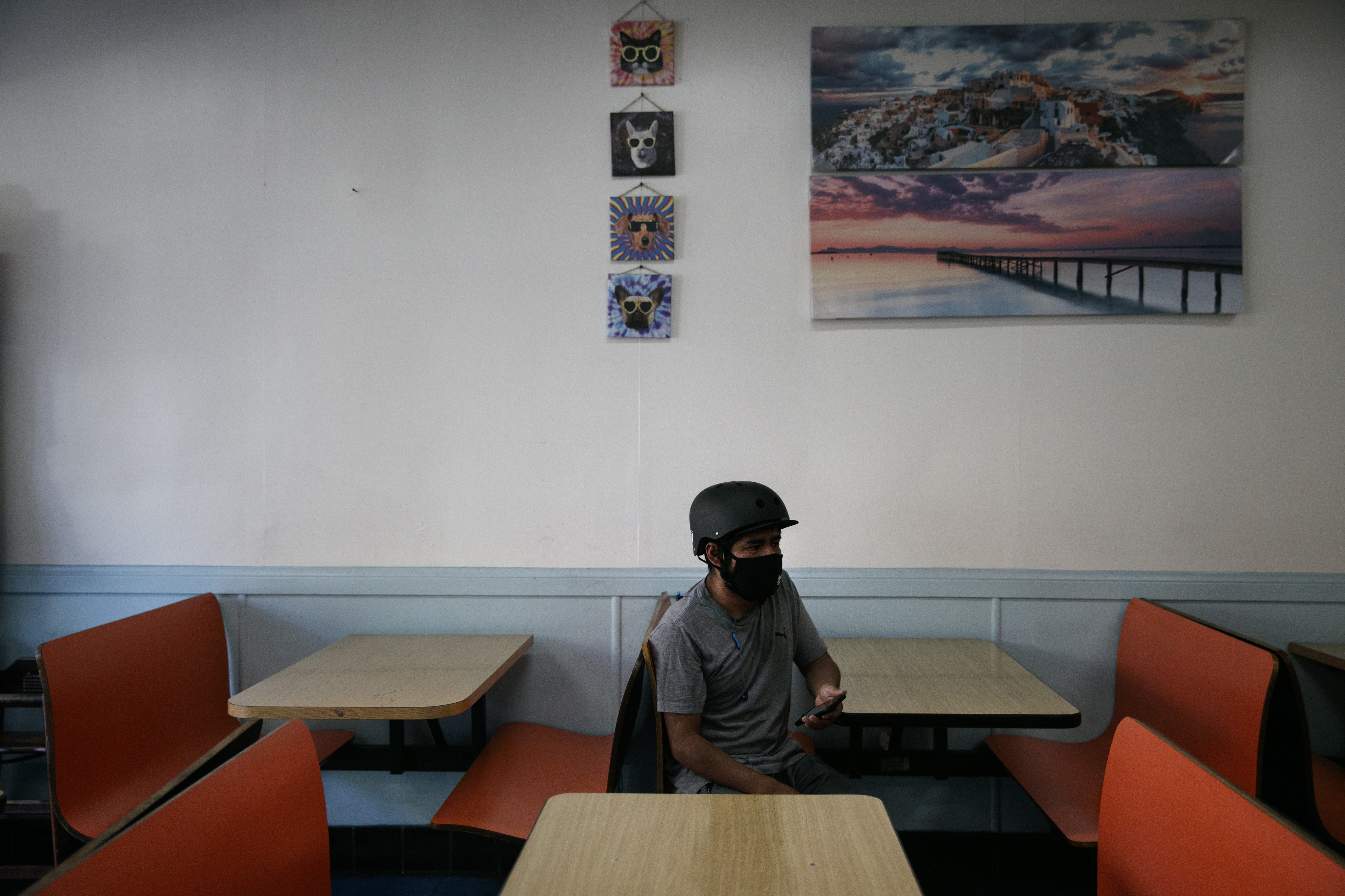 Ronald Rac waits for his order in an empty restaurant amid the coronavirus pandemic in the Westlake neighborhood of Los Angeles, Thursday, May 21, 2020. While most of California took another step forward to partly reopen in time for Memorial Day weekend, Los Angeles County didn't join the party because the number of coronavirus cases has grown at a pace that leaves it unable to meet even the new, relaxed state standards for allowing additional businesses and recreational activities. (AP Photo/Jae C. Hong)