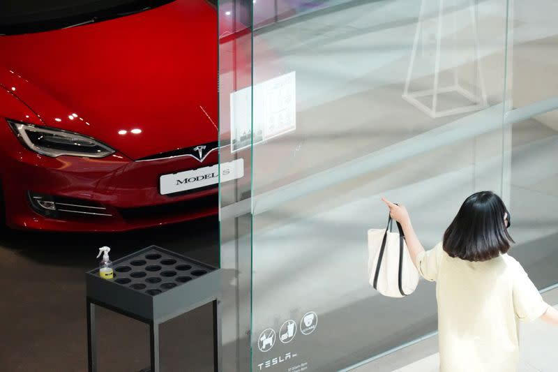 FILE PHOTO: A woman walks past a Tesla dealership in Hanam