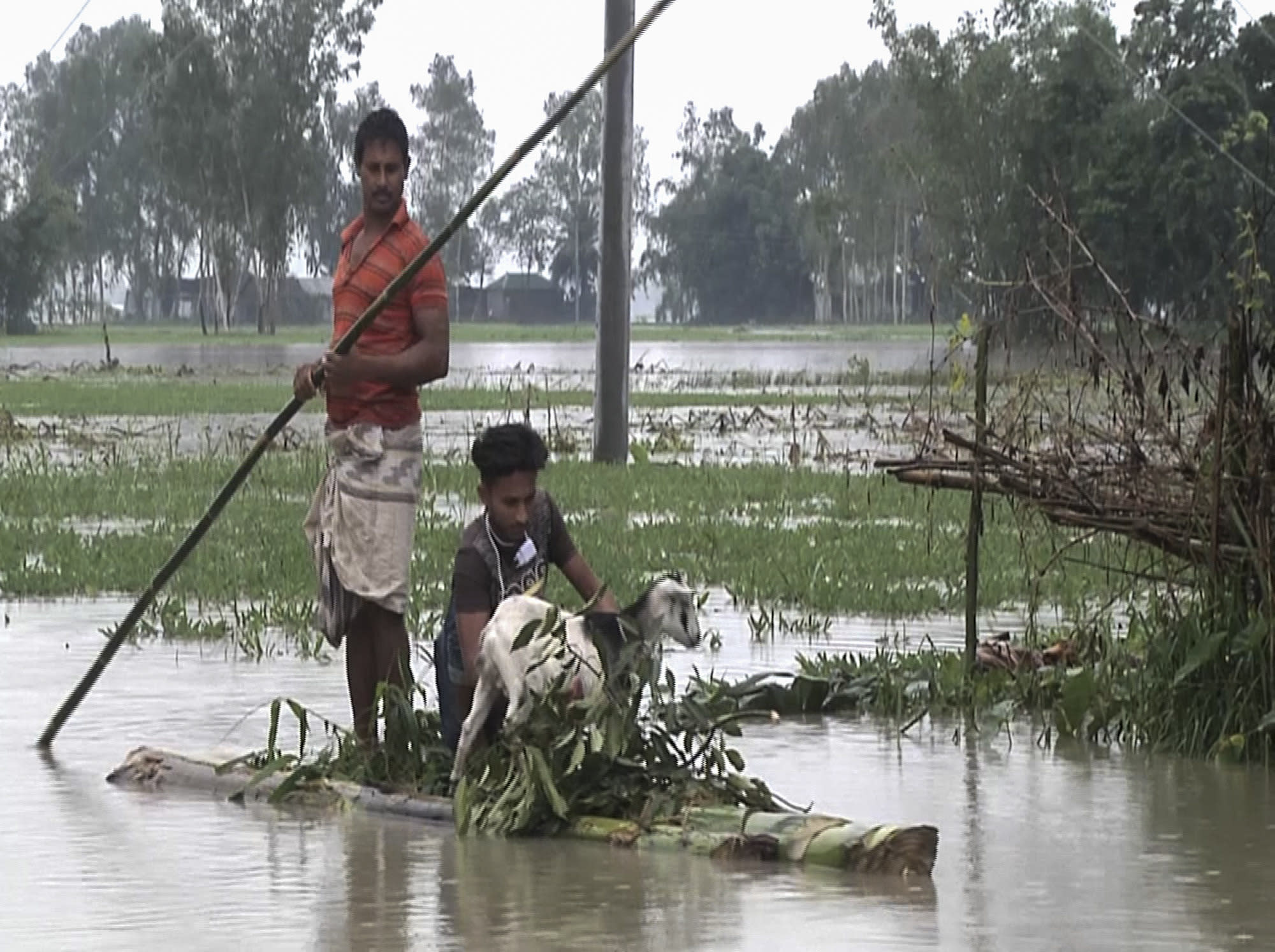 In this video grab taken from the Associated Press Television footage Bangladeshi men with a goat row a banana raft through flood waters in Lalmonirhat, Bangladesh, Monday, July 13, 2020. Heavy flooding is worsening in parts of Bangladesh, with over 1 million villagers marooned or leaving their homes for higher ground along with their cattle and other belongings, officials and volunteers said Tuesday. (AP Photo/Bayezid Ahmed)