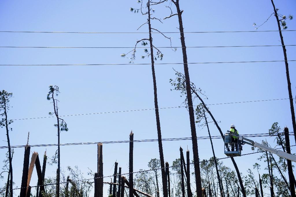 Utility workers have been working nonstop since Hurricane Michael devastated a wide swath of the Florida coast, but many area remain in the dark, without power, phone or internet service (AFP Photo/Brendan Smialowski)
