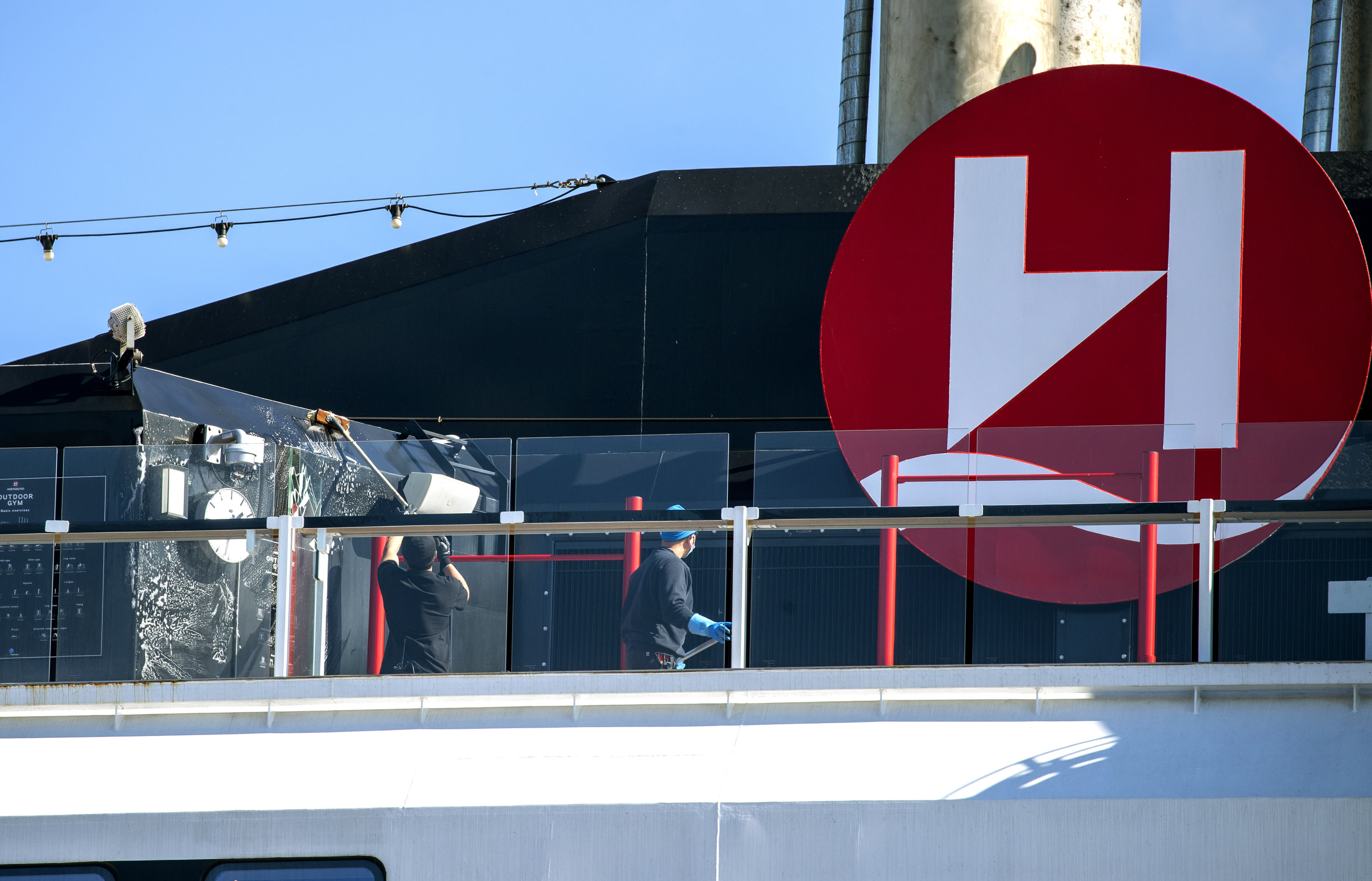 Crew members clean on board Hurtigruten's vessel MS Roald Amundsen, docked in Tromso, Norway, Sunday, Aug. 2, 2020. Over 30 crew members and an unconfirmed number of passengers have so far tested positive for the coronavirus after two international cruises which resumed operation recently, since the outbreak of the coronavirus pandemic. (Terje Pedersen/NTB scanpix via AP)