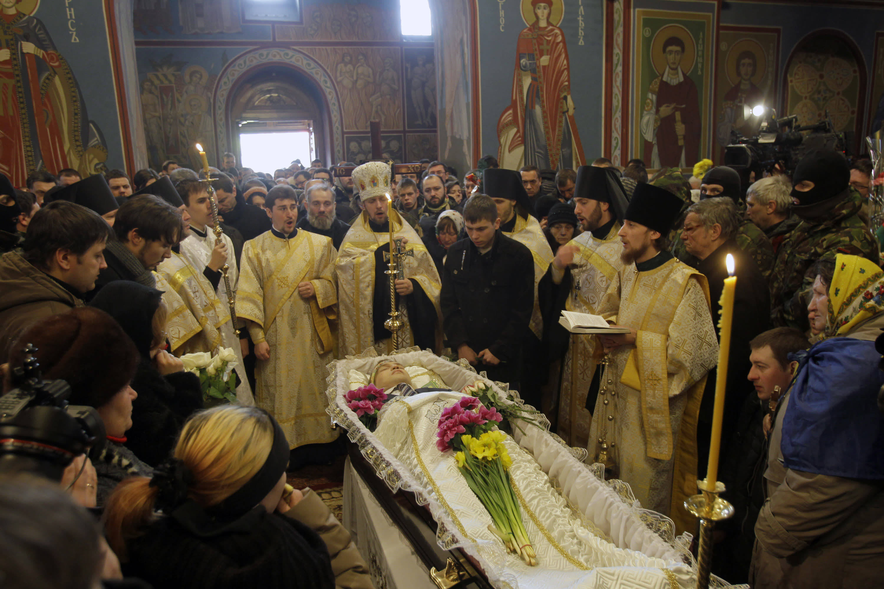 Orthodox Church priests perform a service to commemorate Mikhail Zhiznevsky, 25, one of two protesters who died of gunshot wounds on Wednesday, in Kiev, Ukraine, Sunday Jan. 26, 2014. Ukraine's opposition called off a massive rally planned for Sunday because of the funeral for a protester killed in clashes with police last week, underscoring the rising tensions in the country's two-month political crisis. The opposition contends they were shot by police in an area where demonstrators had been throwing rocks and firebombs at riot police for several days. (AP Photo/Darko Vojinovic)