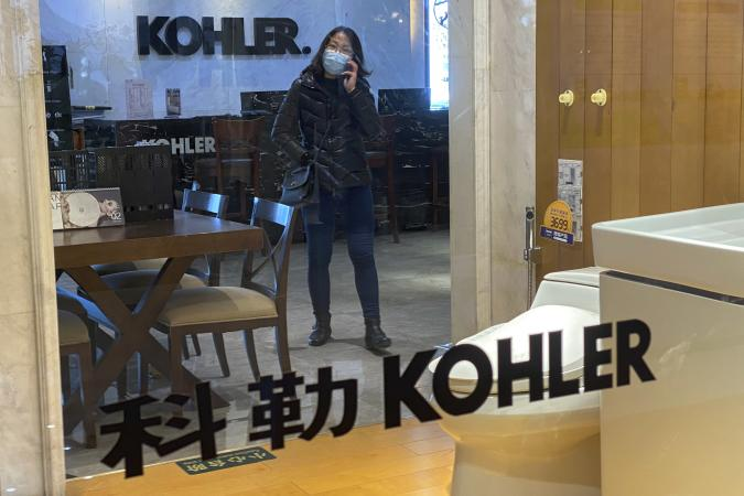 A woman wearing a face mask to help curb the spread of the coronavirus talks on her phone inside a Kohler shop in Beijing, Tuesday, March 16, 2021. Chinese state TV has criticized bathroom fixtures brand Kohler and automaker BMW for using facial recognition to identify customers in a possible violation of privacy rules that took effect this year. (AP Photo/Andy Wong)