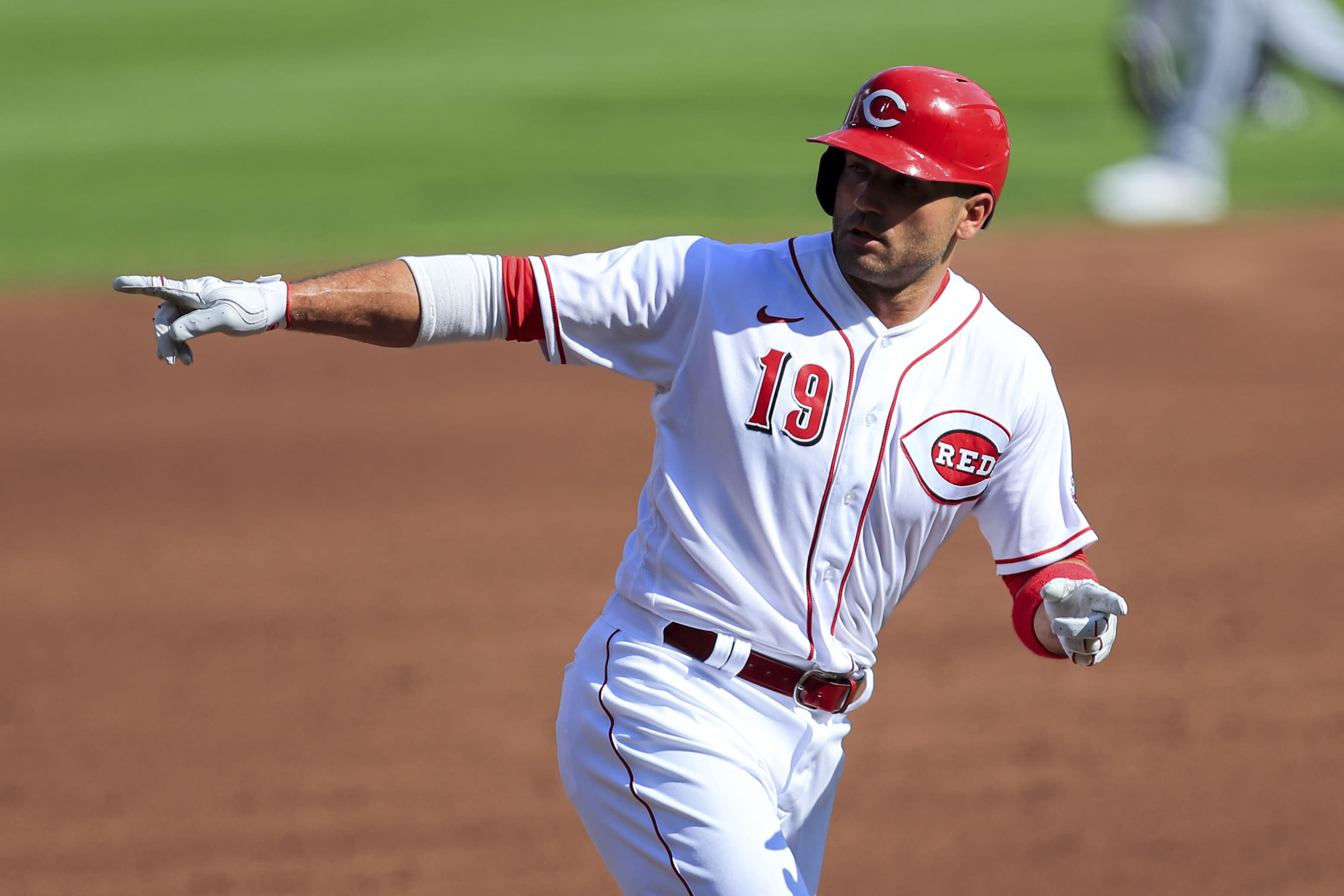Cincinnati Reds' Joey Votto (19) points to members of the grounds crew after he hit a solo home run in the first inning during a baseball game against the Detroit Tigers at Great American Ballpark in Cincinnati, Saturday, July 25, 2020. (AP Photo/Aaron Doster)