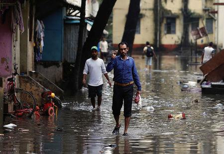 People walk through a partially flooded street at a residential area in Mumbai, India, August 30, 2017. REUTERS/Danish Siddiqui
