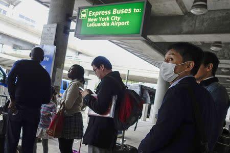 A passenger wears a mask as he exits the International JFK airport in New York October 11, 2014. REUTERS/Eduardo Munoz