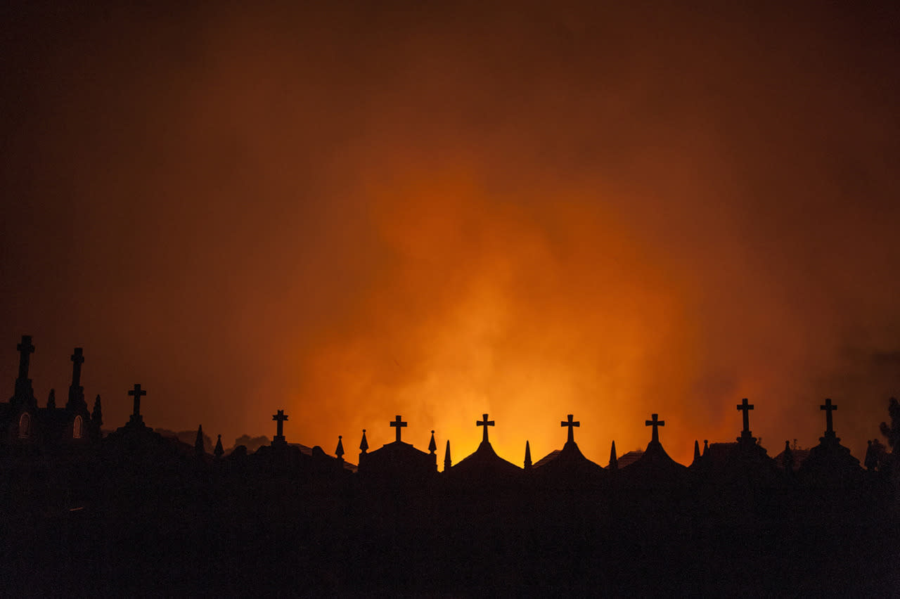 <p>Graves are silhouetted as a fire burns at Espino in Oimbra, Galicia, Spain, Aug. 14, 2016. (Photo:BRAIS LORENZO/EPA)</p>