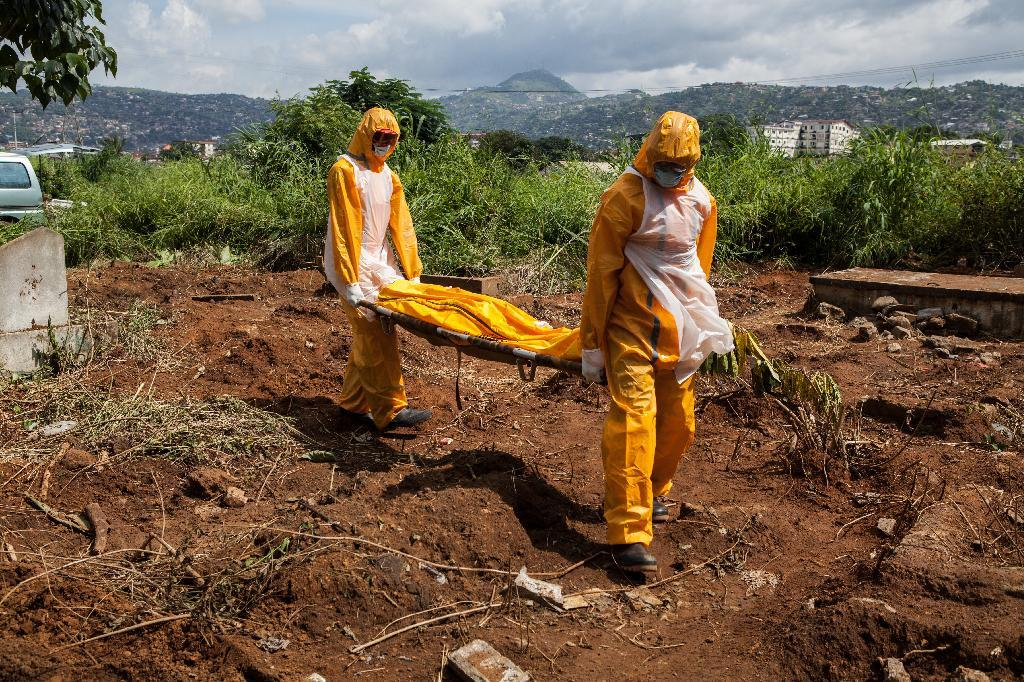 A team of funeral agents specialised in the burial of victims of the Ebola virus carry a body prior to put it in a grave at the Fing Tom cemetery in Freetown, on October 10, 2014 (AFP Photo/Florian Plaucheur)
