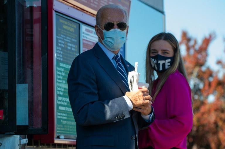 Democratic presidential nominee Joe Biden speaks to reporters after buying two milk shakes at local hamburger place after a campaign stop in Durham, North Carolina on October 18, 2020