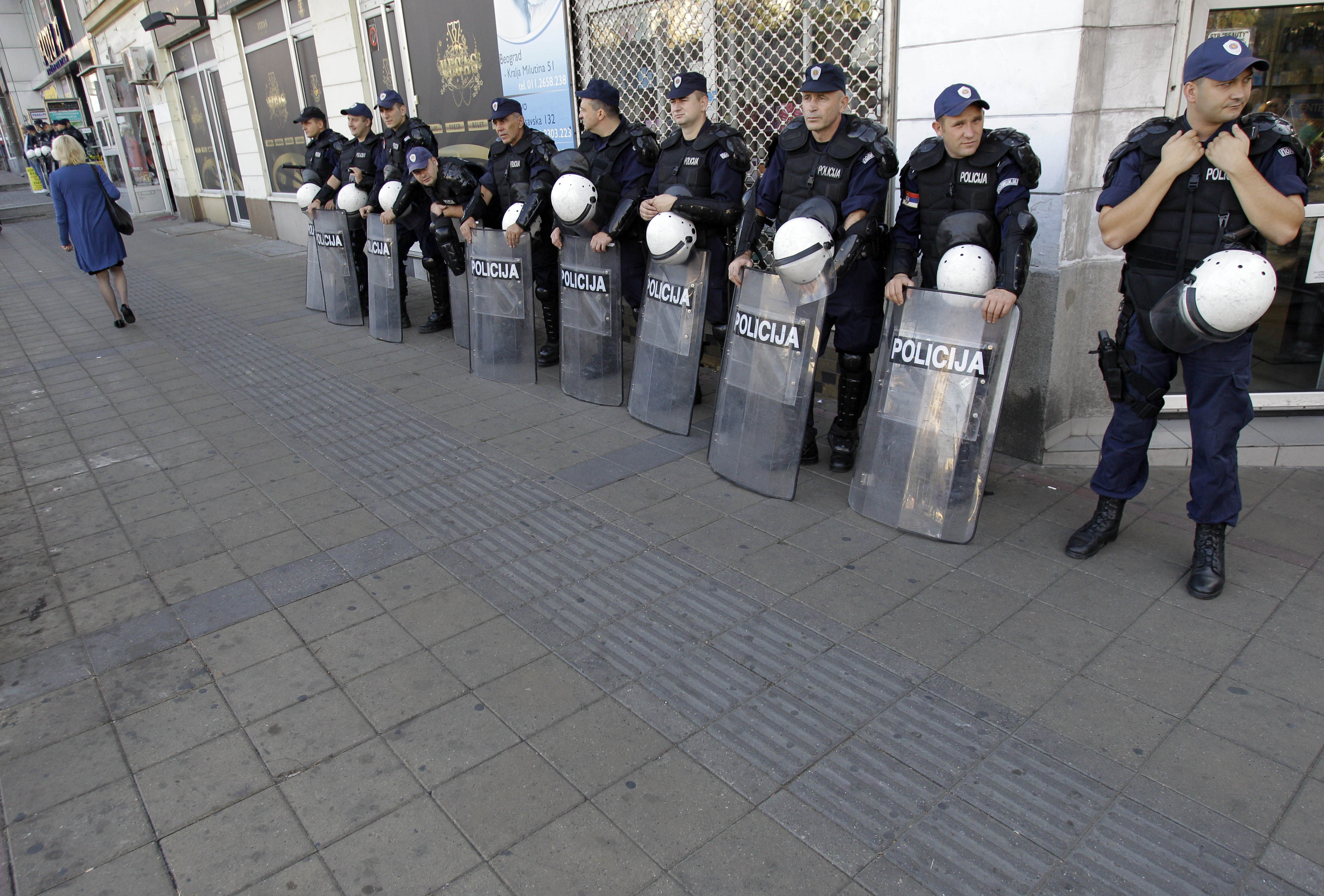 A woman passes by Serbian riot policemen cordon near the an art exhibition gallery in Belgrade, Serbia, Wednesday, Oct 3, 2012. Meanwhile, some 2,000 of riot policemen were deployed on Wednesday in front of an art exhibition in Belgrade organized by gay activists which the extremists had threatened to disrupt. Serbia's police on Wednesday banned a gay pride march in Belgrade, citing security concerns but also complying with a request from Serbia's Christian Orthodox church. (AP Photo/Darko Vojinovic)
