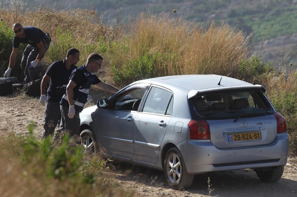 Israeli forensic police inspect a car belonging to Israeli victims of a gun attack by a Palestinian man near the Dolev settlement, northwest of Ramallah in the Israeli-occupied West Bank, on June 19, 2015 (AFP Photo/Abbas Momani)