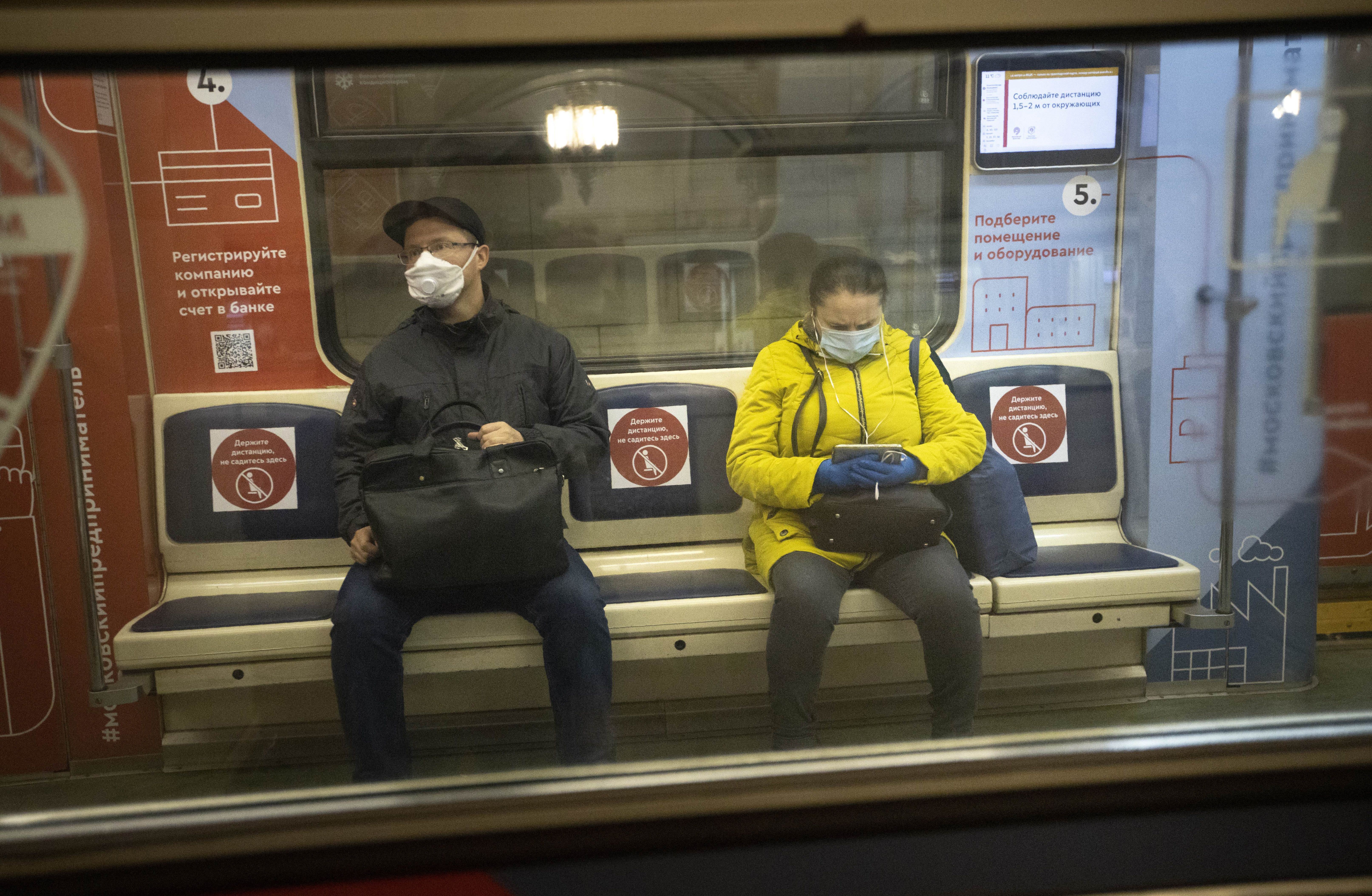 People wearing face masks and gloves to protect against coronavirus, observe social distancing guidelines as they ride a carriage in the subway on the escalator in Moscow, Russia, Wednesday, May 13, 2020. Wearing face masks and latex gloves is mandatory for people using Moscow's public transport. President Vladimir Putin declared an end to a partial economic shutdown across Russia due to the coronavirus pandemic, but he said that many restrictions will remain in place. (AP Photo/Alexander Zemlianichenko)