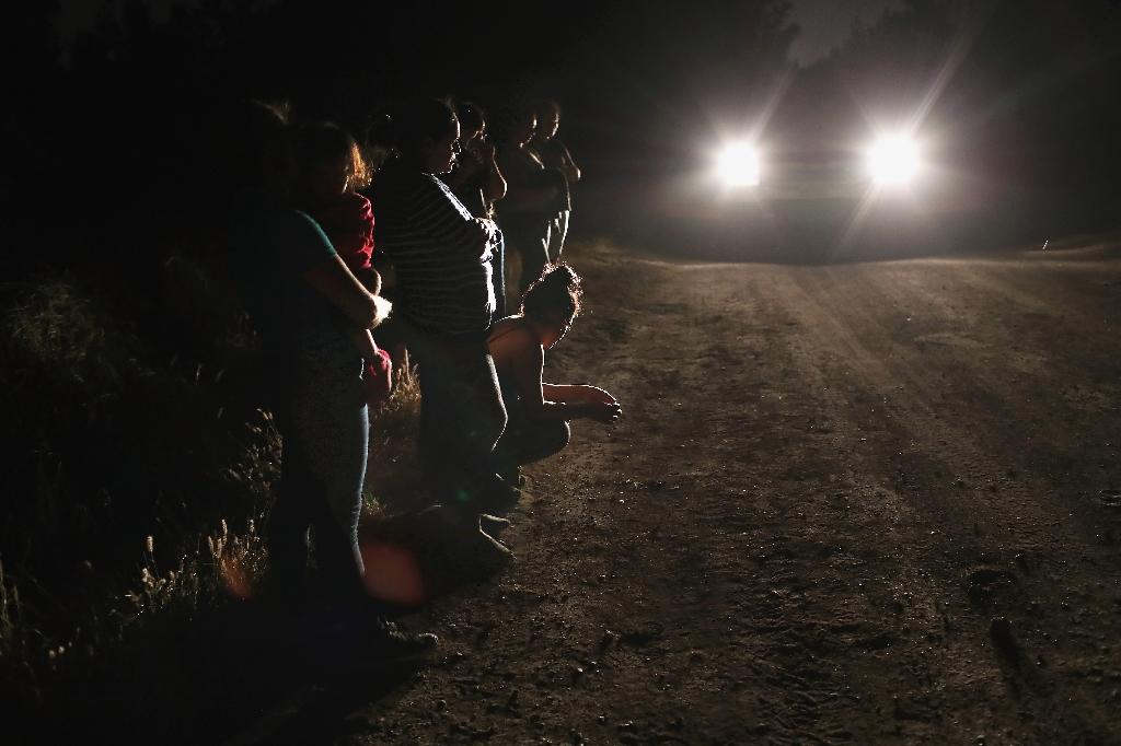Migrants in McAllen, Texas, are seen as agents arrive to take them into custody -- it fell to Nielsen to carry out US President Donald Trump's anti-immigration policies (AFP Photo/JOHN MOORE)