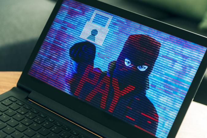 Criminal hiding behind a mask turns up on computer screen asking the owner for money. Concept of phishing and ransomware, where the computer has all files on the harddrive encrypted and the victims need to pay a ransom in order to get their files unlocked.
