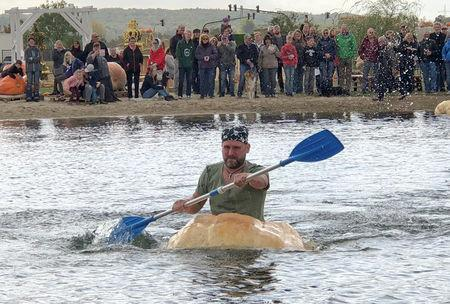 A man paddles his giant pumpkin boat during the raditional pumpkin race in Lohmar, Germany October 3, 2018. Reuters/David Sahl
